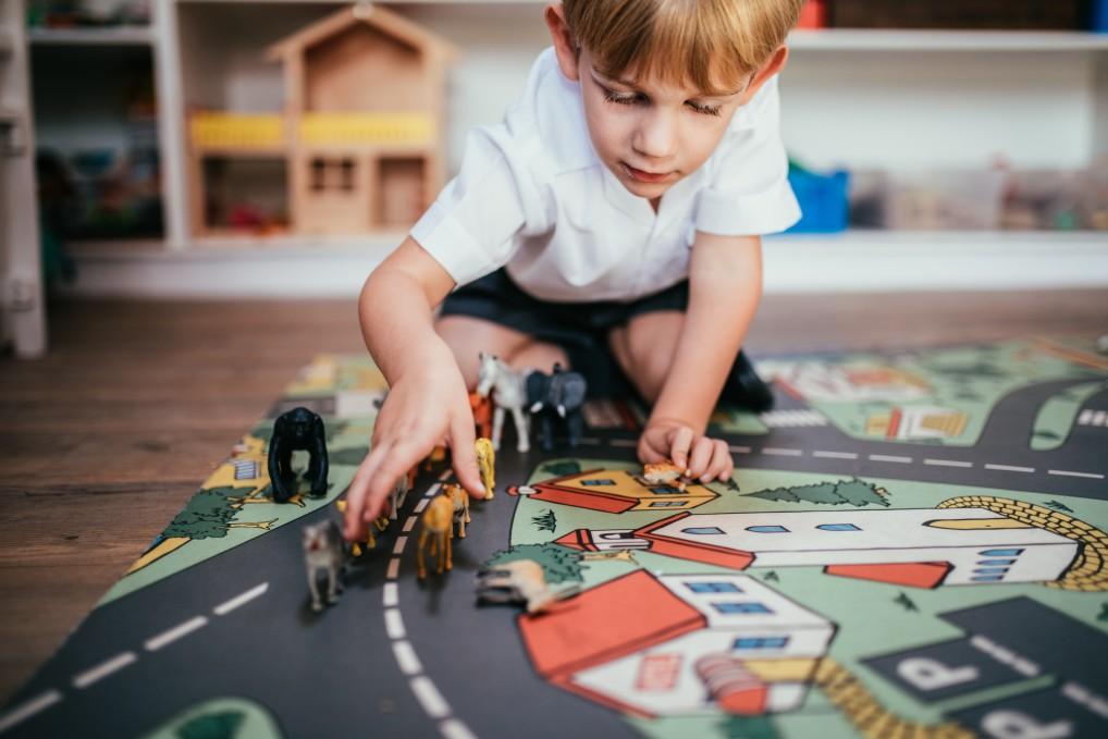 Junge spielt mit Tierfiguren