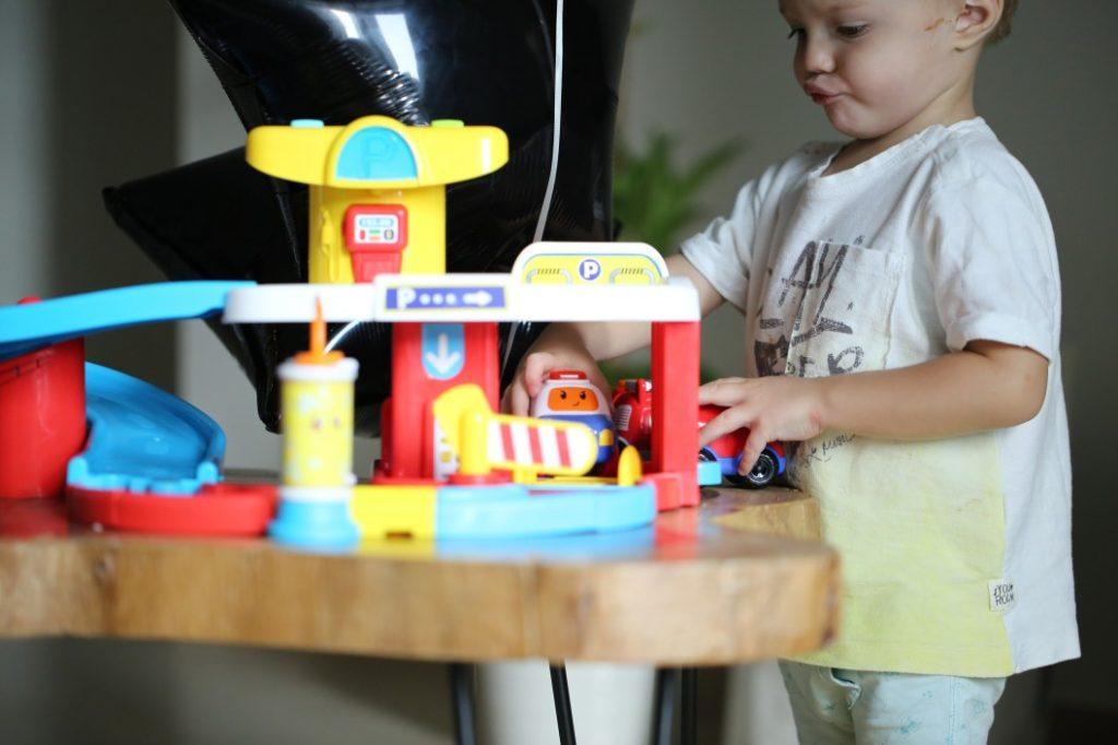 Kind spielt mit Parkhaus für Spielzeugautos