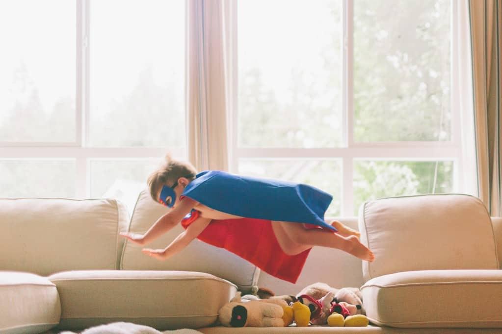 Kind tobt im Wohnzimmer