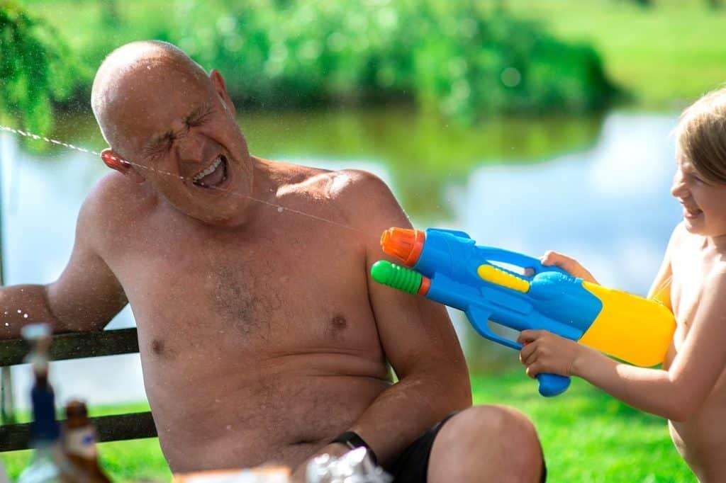 Mädchen schießt mit Wasserpistole auf Opa