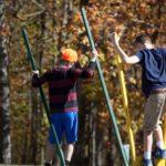 Kinder laufen im Herbst auf Stelzen