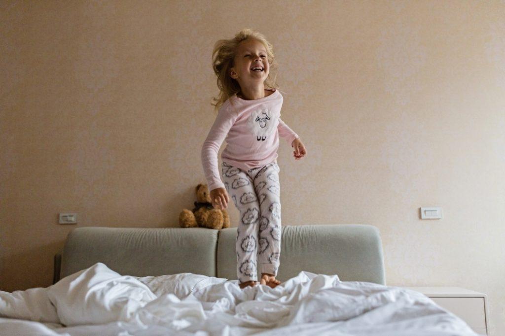 Mädchen hüpft im Bett